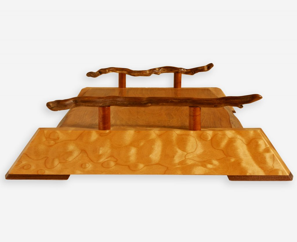 A delightful live edge Arbutus and Quilted Maple serving platter with driftwood handles to counter the sharp angular form of the maple base.
